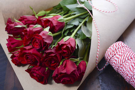 Wrapping Valentine red roses in brown paper on dark wood background.