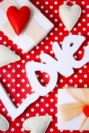 joining the dots: Valentine red polka dot background with Love wooden letters, hearts and gifts.