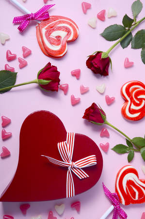 scattered in heart shaped: Happy Valentines Day pink background with scattered lollipops, roses and heart shaped gift.