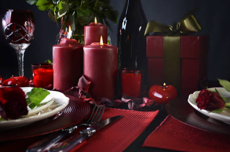 candle light table setting: Romantic candle light Valentine Table Setting for two with red roses, gift and burning candles against a black background. Stock Photo