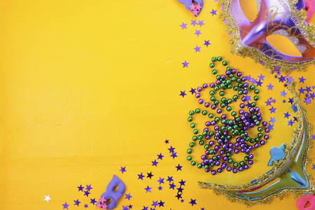 Mardi Gras masks with party decorations, beads and glitte stars.