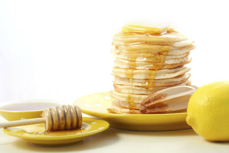 drizzle: Pancakes served with lemon and honey on yellow plates on a white wood table.