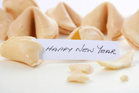 fortune cookie: Happy Chinese New Year message inside closeup of fortune cookies on a white wood table.