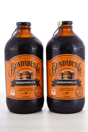 family owned: ADELAIDE, AUSTRALIA - NOVEMBER 15, 2015: Australian Bundaberg Sarsaparilla carbonated soda pop soft drink bottles on white wood table.