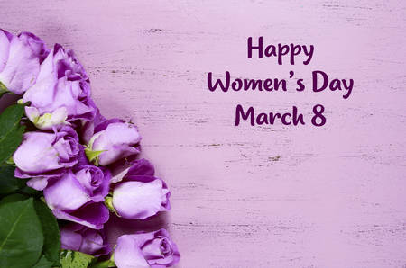 International Womens Day purple roses on purple wood background with copy space and sample text.