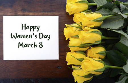 Internationale Vrouwendag gift van gele rozen met een wenskaart en voorbeeld tekst. Stockfoto