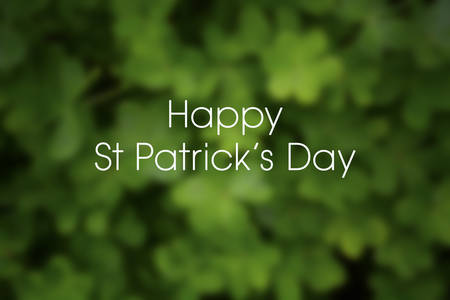 Blurred background of green shamrock clover for St Patricks Day, with sample greeting text.