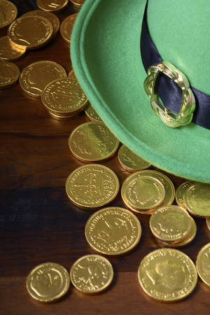 paddys day: Happy St Patricks Day green leprechaun hat with gold covered chocolate coins on dark wood background.