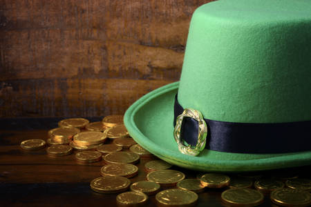 saint paddy's: Happy St Patricks Day green leprechaun hat with gold covered chocolate coins on dark wood background.