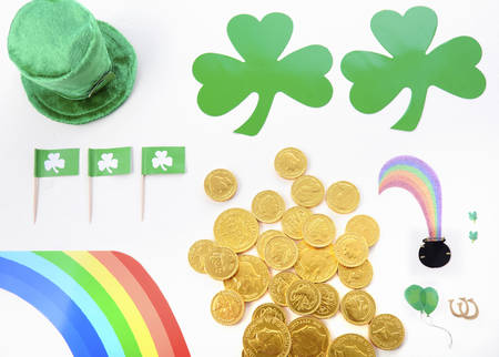 st  paddy's day: St Patricks Day Flat Lay including leprechan hat, chocolate gold covered coins and shamrocks on white wood background.