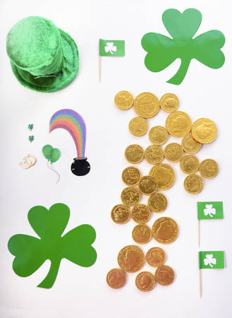 St Patricks Day Flat Lay including leprechan hat, chocolate gold covered coins and shamrocks on white wood background.