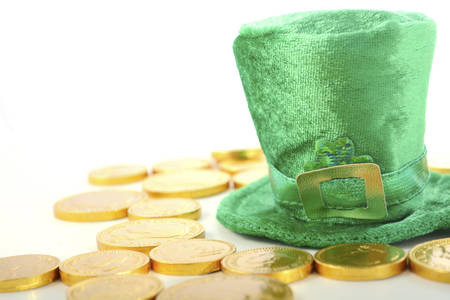 st  paddy's day: St Patricks Day leprechaun hat with chocolate gold covered coins on white wood backround.