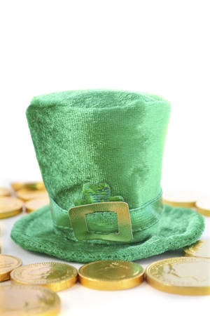 St Patricks Day leprechaun hat with chocolate gold covered coins on white wood backround.