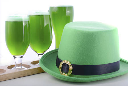 tradional: St Patricks Day line up of of glasses of green beer with leprechaun hat on a white wood table background. Stock Photo