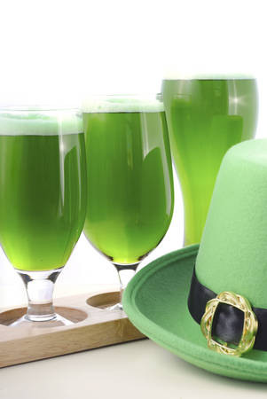 st  paddy's day: St Patricks Day line up of of glasses of green beer with leprechaun hat on a white wood table background. Stock Photo