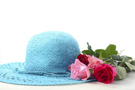 Ladies sun hat and roses on a white wood table for International Womens Day, March 8.