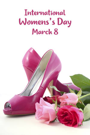 Women s shoes: Feminine pink high heel shoes with roses on white wood table for International Womens Day, March 8.