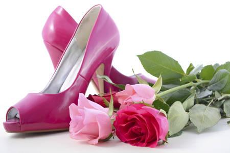 Zapatos rosados ??femeninos de tacón alto con rosas en la mesa de madera blanca para el Día Internacional de la Mujer, 8 de marzo. Foto de archivo - 54232512