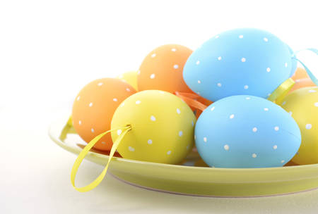 good friday: Happy Easter bright blue, yellow and orange polka dot Easter Eggs on green plate on white wood background. Stock Photo