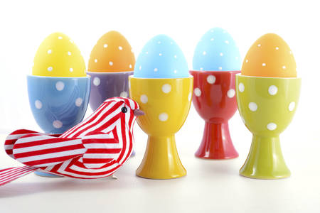 egg cups: Happy Easter bright blue, yellow and orange polka dot Easter Eggs in egg cups with ornamental bird on white wood background.
