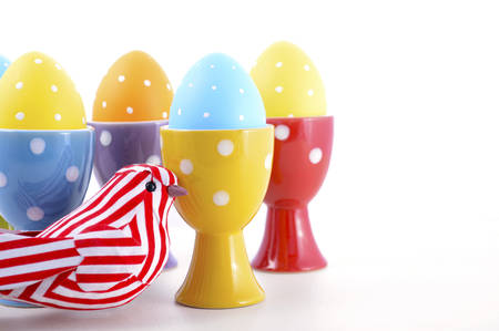 egg cups: Happy Easter bright blue, yellow and orange polka dot Easter Eggs in egg cups with ornamental bird on white wood background, with copy space.
