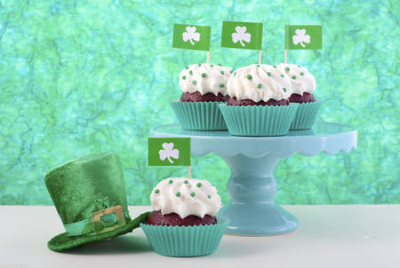 Happy St Patricks Day cupcakes with shamrock flags and green leprechaun hat against a green background on a white wood table.