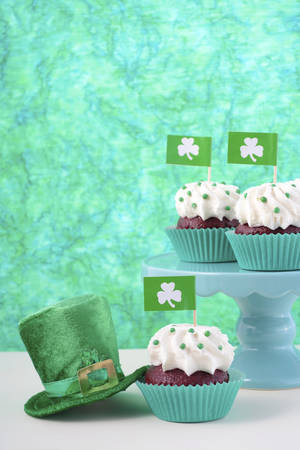 saint paddy's: Happy St Patricks Day cupcakes with shamrock flags and green leprechaun hat against a green background on a white wood table.