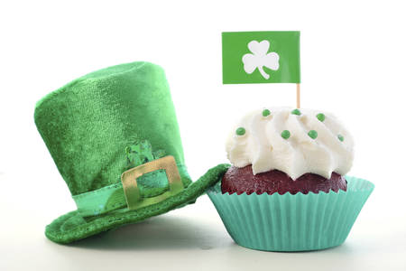 saint paddy's: Happy St Patricks Day cupcake closeup with shamrock flags and green leprechaun hat on a white wood table. Stock Photo