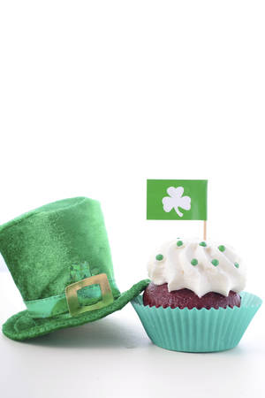 paddys day: Happy St Patricks Day cupcake closeup with shamrock flags and green leprechaun hat on a white wood table. Stock Photo