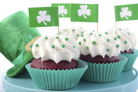 red velvet cupcake: Happy St Patricks Day cupcakes with shamrock flags on a cake stand with a green leprechaun hat on a white wood table. Stock Photo