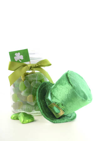 st  paddy's day: Happy St Patricks Day jar of green candy with leprechaun hat on a white wood table.