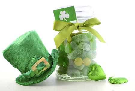 Happy St Patricks Day jar of green candy with leprechaun hat on a white wood table.