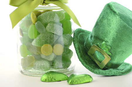 Happy St Patricks Day jar of green candy with leprechaun hat on a white wood table, closeup. Stock Photo