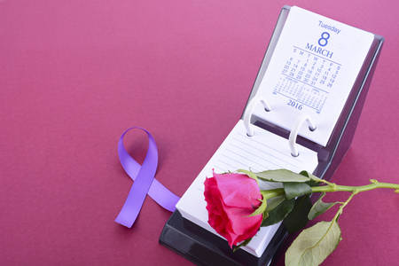 a stem here: Desk calendar for March 8, International Womens Day, with rose bud and purple ribbon symbol, on pink background, with copy space.