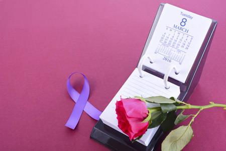 Tischkalender für 8. März, Internationaler Frauentag, mit Rosenknospe und lila Band-Symbol, auf rosa Hintergrund, mit Kopie Raum.