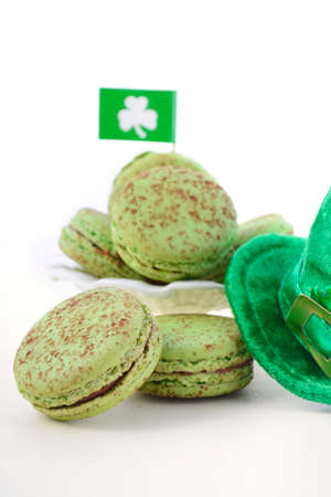 paddys: St Patricks Day green macarons with shamrock flags and leprechaun hat on white wood table background.