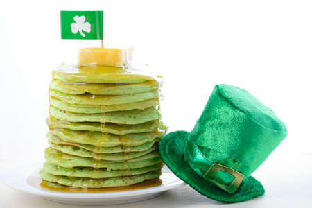 St Patricks Day green pancakes with drizzling syrup, shamrock flag and green leprechaun hat.