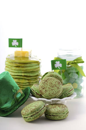 St Patricks Day party food green macarons, candy jar and stack of green pancakes with shamrock flags and leprechaun hat on white wood table background. Stock Photo