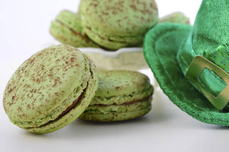 st  paddy's day: St Patricks Day green macarons with shamrock flags and leprechaun hat on white wood table background, closeup.