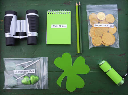 paddys day: St Patricks Day Catch a Leprechaun Kit gift with binoculars, torch, field notes notepad, pencils, and candy and coins leprechaun bait bags on green wood background.
