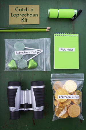 st  paddy's day: St Patricks Day Catch a Leprechaun Kit gift with binoculars, torch, field notes notepad, pencils, and candy and coins leprechaun bait bags on green wood background.