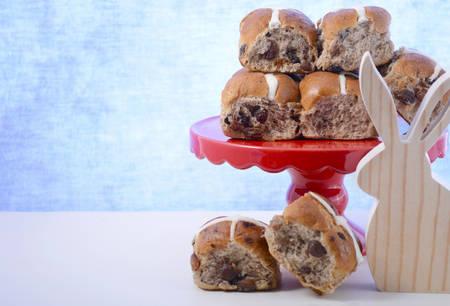 bollos: Happy Easter bollos cruzados calientes en soporte de la torta de color rojo y la decoración del recorte del conejito madera en la mesa de madera blanca con el fondo de color azul pálido, con copia espacio.