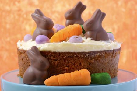 ?  ? carrot: Pastel de zanahoria de Pascua decorado con mini zanahorias y pasta de azúcar conejos de chocolate en una mesa de madera blanca con fondo naranja, primer plano.