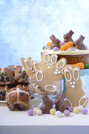 bollos: banquete comida feliz del partido del partido de Pascua de Alimentos Wiith pastel de zanahoria, bollos cruzados calientes, galletas de jengibre y mini conejo conejo de chocolate y caramelo de los huevos de Pascua verticales, con copia espacio.
