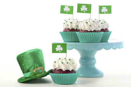 Happy St Patricks Day cupcakes with shamrock flags on a cake stand with a green leprechaun hat on a white wood table. Stock Photo