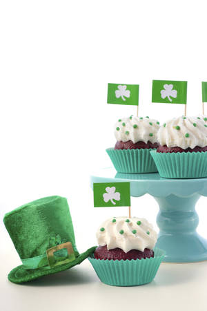 paddys: Happy St Patricks Day cupcakes with shamrock flags on a cake stand with a green leprechaun hat on a white wood table. Stock Photo