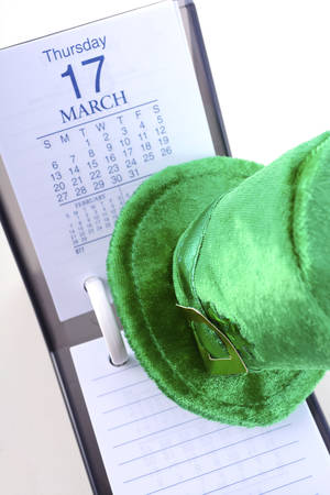 st  paddy's day: St Patricks Day calendar for March 17 with green leprechaun hat on white wood table.