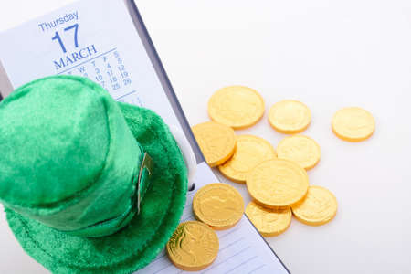 march 17: St Patricks Day calendar for March 17 with green leprechaun hat and gold covered chocolate coins on white wood table.