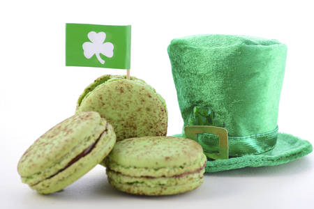 St Patricks Day green macarons with shamrock flags and leprechaun hat on white wood table background.