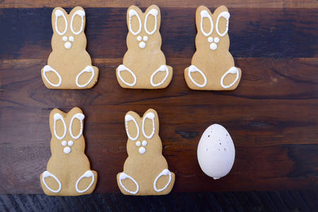 easter cookie: Happy Easter gingerbread cookie bunnies on a dark wood table background.